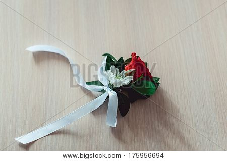 little luxury wedding boutonniere with roses with white ribbon on the table