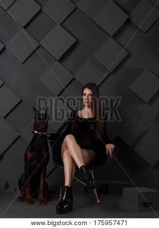 Young sexy brunette in black bodysuit with angry doberman dog siitting on the chair. Cube background