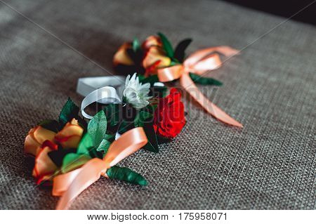 three little luxury wedding boutonniere with roses with ribbon on the corner of the table. Gray textile background