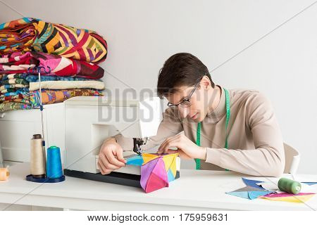 handsome young male tailor in eyeglasses sewing a colored patchwork quilt on the sewing machine on a white background. production of scrappy blankets.