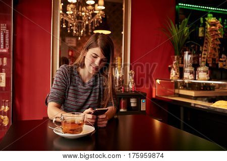 Smiling Young Lady Sitting In A Bar