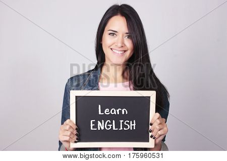 Young Woman Holding Chalkboard That Says Learn English