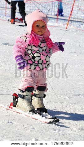 Portrait of little girl skier in sports suit with ski