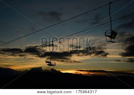 empty ski lift / chairlift silhouette on high mountain over the clouds at sunset