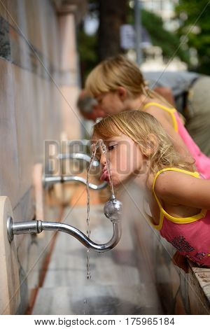 A girl drinks water from fountain in the park