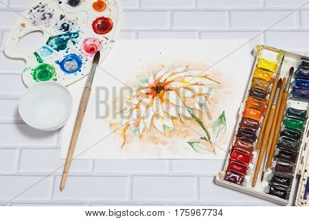 Hand Drawn Bright Sketch of Orange Lily Flower with lying paints paintbrushes and palette on the white brick background - concept of human creativity perspective view