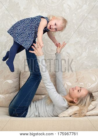 Young mother is playing with her daughter