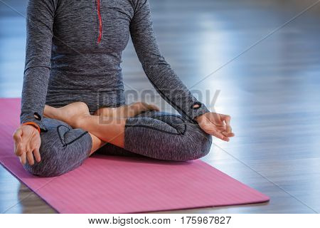 fitness, sport, yoga and healthy lifestyle concept - close up of woman meditating in easy sitting pose on pink yoga mat in gym. Blue sportwear. Healthy lifestyle.
