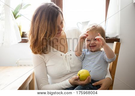 Mother And Child Having Fun Time Toghether At Kitchen