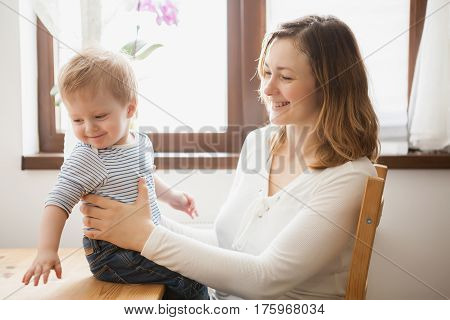 Happy Mother With Her Child At Kitchen