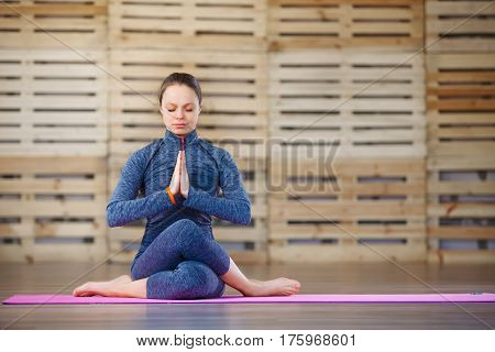 Girl sitting in a yoga pose gym. Relaxation meditation health. Woman in the blue sportwear. On the pink yoga mat. In gym. Portrait. Health lifestyle.