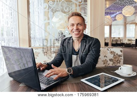 Young man in a cafe waiting for a meeting, freelancer