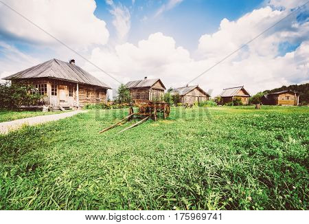 Old wooden cart on the green grass on the background of village houses