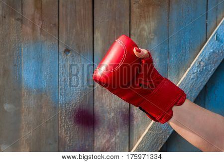 Red leather boxing glove on a woman's hand empty space on the left