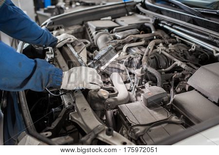 Mechanic hands checking up of serviceability of the car in open hood, close up.