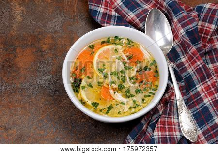 Homemade tender soup with chicken lemon orzo and fresh parsley leaves