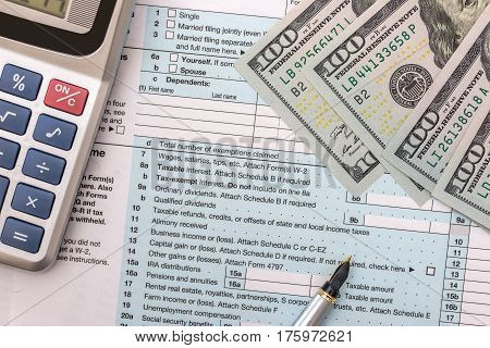 1040 Tax Form With Calculator, Pen, Glasses, And Dollar Banknote; Finance Concept.