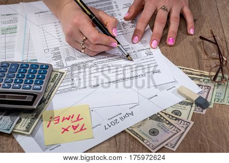 woman filling tax forms. 2017 close up