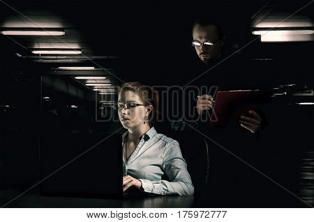 Suspicious man controls work of a woman in a dark room. The concept of hard work under pressure