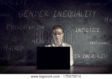 Woman works at her desk in a dark room. The concept of gender intolerance and prejudice