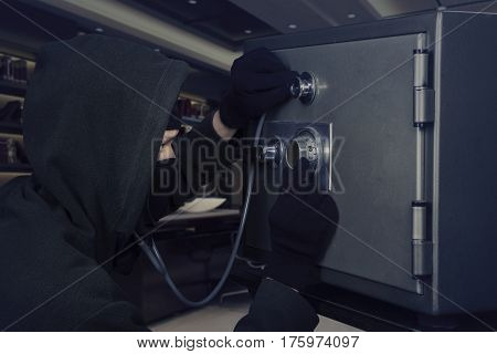 Male burglar wearing a mask and using a stethoscope to open a bank vault in the office at night