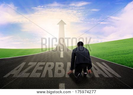 Young businessman kneeling on the road and ready to chase success in the Azerbaijan country