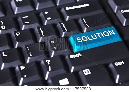 Closeup of computer keyboard with solution word on the blue button