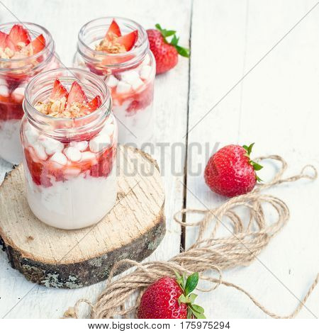 Fresh milk yoghurt with strawberries marshmallow and granola served in a glass jars on white wooden table with place for text. Healthy summer breakfast concept. Selective focus. Copy space. square.