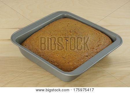 Baked gingerbread cake in baking pan on table