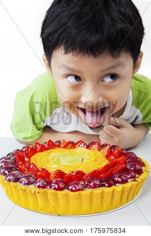 Portrait of a funny little boy sticking his tongue out with a delicious pie on the table