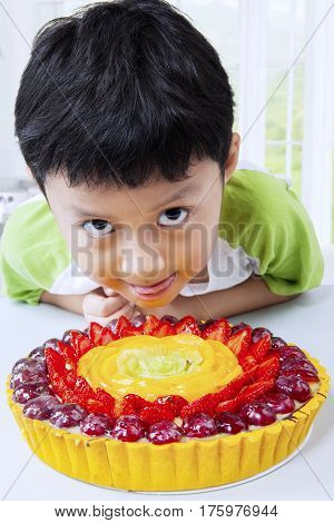 Portrait of a cute little boy looking at the camera with a tasty fruit pie on the table in the kitchen