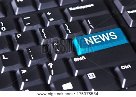 Closeup of modern keyboard with news word on the blue button