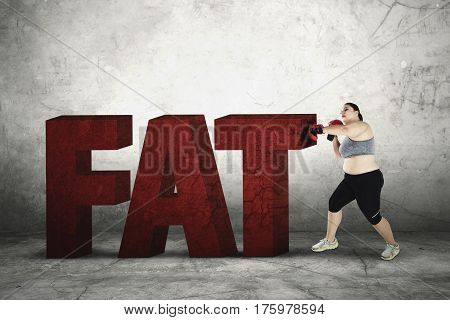 Portrait of an obese woman wearing boxing gloves to crushing word of fat