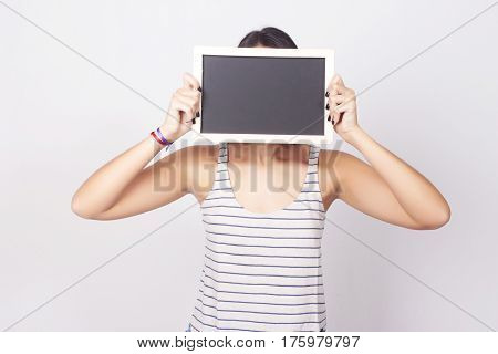 Beautiful young woman holding and showing something on a chalkboard. Copyspace.