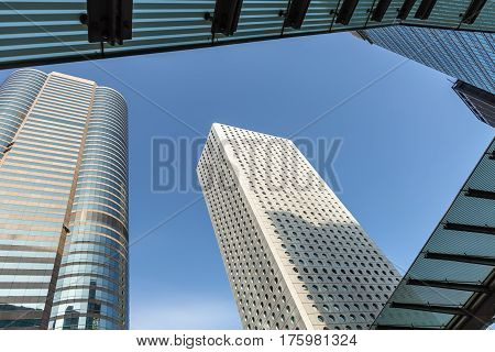 Few skyscrapers on the blue sky background in Singapore. View from below. Horizontal.
