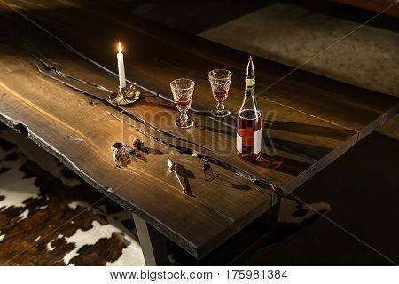 Stylish dark wooden table in the poor lighted room. There is a burning candle, two glasses with drinks, bottle with a bung, cork and accessories. Closeup. Horizontal.