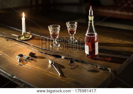 Fashionable dark wooden table in the poor lighted room. There is a burning candle, two glasses with drinks, bottle with a bung, cork and accessories. Closeup. Horizontal.