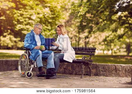 Caring nurse talking with patient in wheelchair checking up the history of the disease