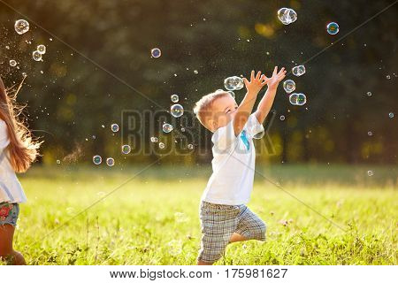 Cute male child catches soap bubbles in nature