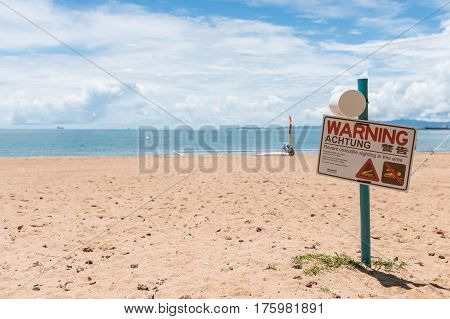 Warning sign for crocodile sighting on Townsville beach The Strand swimming nets in background