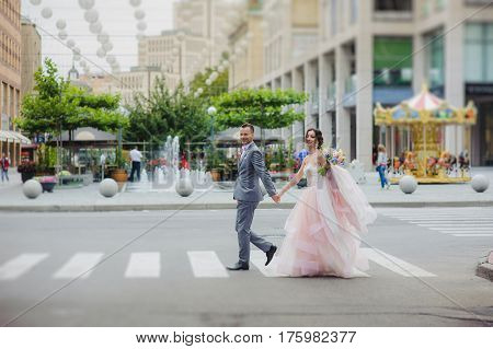 Happy newlyweds cross the street. Happy newlyweds looking at camera.