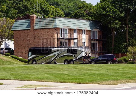 HARBOR SPRINGS, MICHIGAN / UNITED STATES - August 4, 2016: A tour bus is parked outside of an apartment building in Harbor Springs, Michigan.