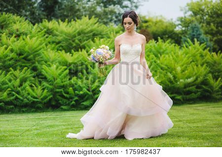 Portrait of a beautiful bride in park. Cute lady with a bouquet in pink wedding dress outdoors. Look down. Grass, trees and bushes in the background.