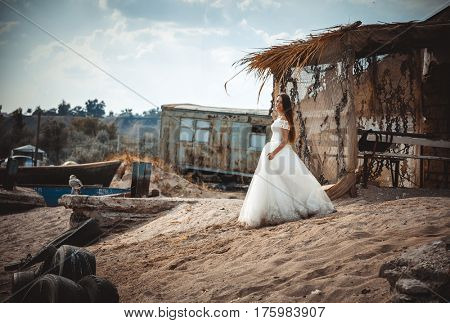 Happy bride near the old fishing dam on the seashore