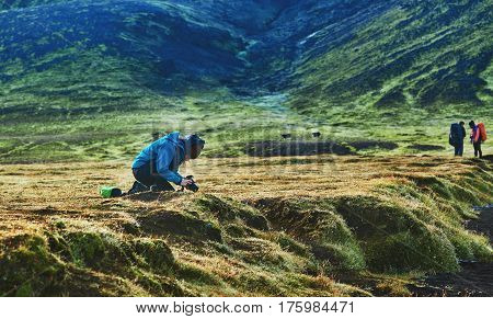 hiker on the trail in the Islandic mountains. Trek in National Park Landmannalaugar, Iceland. woman doing a picture moss on the phone