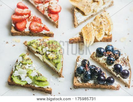 Healthy breakfast wholegrain bread toasts with cream cheese, various fruit, seeds and nuts. Top view, grey marble background. Clean eating, vegetarian, dieting, slow food, healthy lifestyle concept