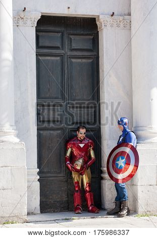 LUCCA ITALY - OCTOBER 29 2011: Captain America and Iron Man standing in front of the Cathedral's gate during the Lucca comics and games annual festival in Italy