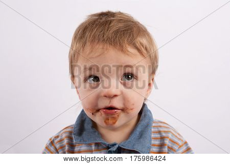 Portrait of a funny baby boy with mouth covered with chocolate