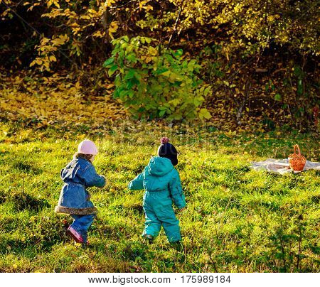 Kids Playing In Autumn Park. Children Play Outdoors On A Sunny Fall Day. Boy And Girl Running Togeth
