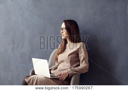 Beautiful businesswoman with long hair using modern laptop computer while sitting in his modern loft office. Dark blue wall background day light